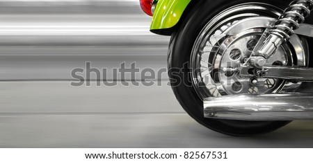 Part of a luxury motorcycle with blurry asphalt road