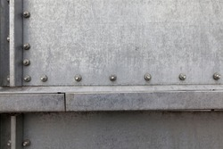part of a metal barrel connected from metal sheets with bolts and rivets