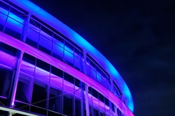 Part of a modern building with neon lighting at night against a dark sky.
