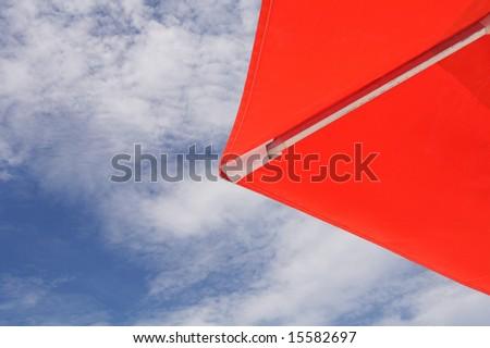Part of a  orange umbrella and blue sky as background