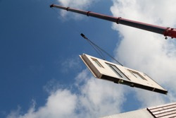 Part of a prefabricated house is assembled with a crane
