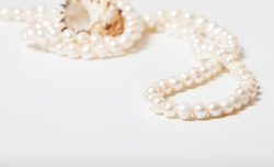 Part of a strand of natural pearls in focus on a white background. The background with a sea shell is blurred.