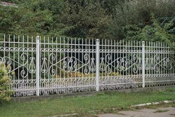 part of a white metal fence made of iron rods with a forged pattern in green grass outside