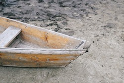 Part of a wooden boat rowboat is moored on the sand and mud near the shore. Background for sailing