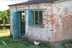 part of an old brick house, with wooden window frames without glass and an open wooden door, a chicken runs near the house