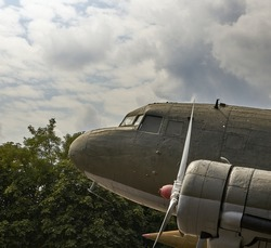 Part of an old World War II military aircraft. Background of sky and trees.