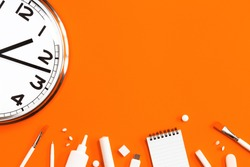 Part of analogue plain wall clock on trendy orange background with white stationery items. One o'clock. Close up with copy space, time management or fall school concept and opening hours time
