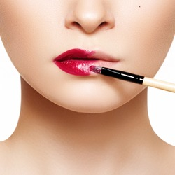 Part of attractive woman's face with fashion red lips makeup. Make-up artist apply bloody lipstick