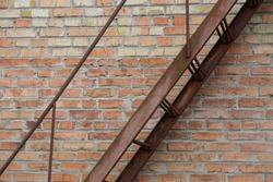 part of brown iron rusty staircase with steps and handrails against a brick wall in the street