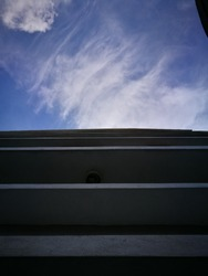 Part of buildings with upward angle towards blue sky and white clouds