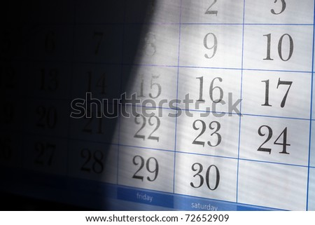 Part of calendar with month end dates with shallow depth of field and half in deep shadow