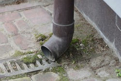 part of dirty brown gutter pipe on gray wall above sidewalk in street