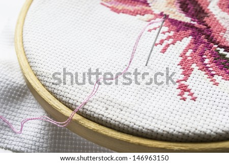 Part of embroidery on wooden hoop with a needle with pink thread closeup