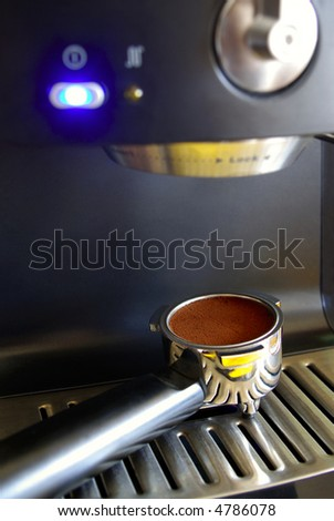 Part of espresso machine with filter holder full of a coffee dose.