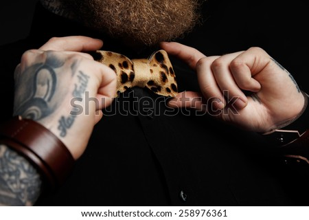 Part of face of the man with beard in black shirt and leopard bow tie. Isolated on dark gray background