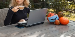Part of face of  young woman sitting in garden at table, working at  laptop, drinking cappuccino. Halloween decorations from   orange pumpkins. Work from home, coffee break, distance learning