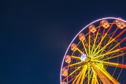 Part of ferris wheel against a blue sky background with lights neby night lighting