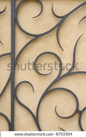 Part of forged gate. Beautiful metal work. Black metal on pastel background.