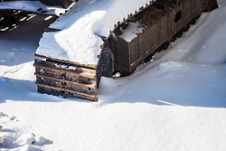 Part of heavy industrial tracks casting shadow on snow.