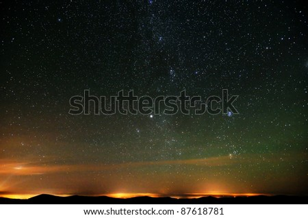 Part of Milky way over city lights and mountains natural photo