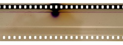 Part of 35mm cine filmstrip, first frames on white background, real scan of film material with cool scanning light interferences on the material.
