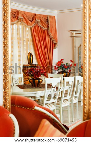 Part of modern art deco style dining room interior with striped vase and red flowers reflected in mirror with golden frame