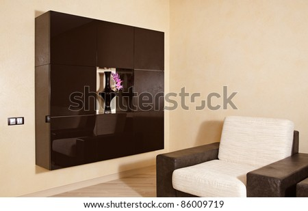 Part of modern interior in warm tones with armchair and niche