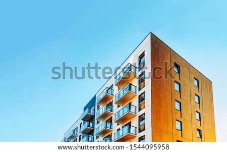 Part of Modern residential apartment with flat building exterior. Detail of New luxury house and home complex. Fragment of City Real estate property and condo architecture. Copy space. Blue sky