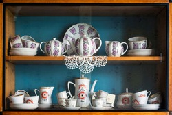 Part of old cabinet with two different sets of tea service (white, decorated with flowers). Detail of typical soviet style apartment interior.