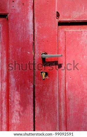Part of old red wooden door with metal handle.