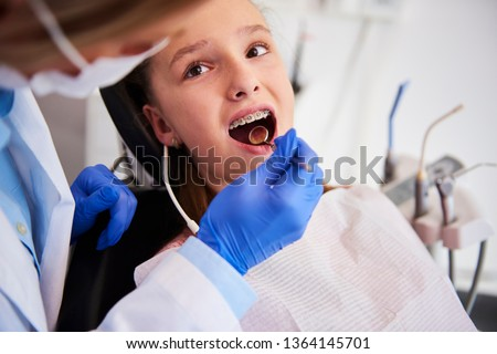 Part of orthodontist examining child's teeth in dentist's office #1364145701