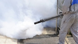 Part of outdoor healthcare worker using fogging machine spraying chemical to eliminate mosquitoes and prevent dengue fever at general location in community