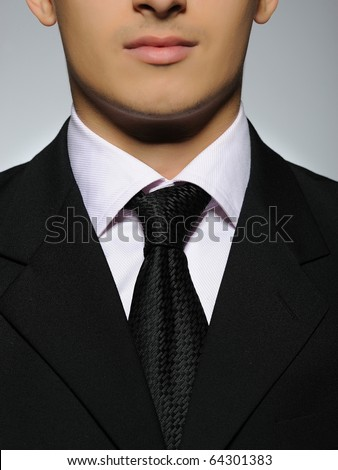part of Portrait of succesful  business man in formal suit and black tie. gray background