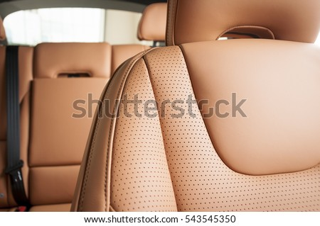 Part of red leather car seat with the unfocused car interior on the background