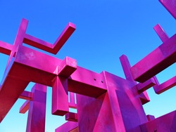 part of statue in pink on a blue sky