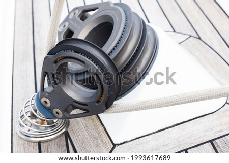 Part of the deck of a sailing yacht with fixing rollers and ropes on them and fasteners for attaching sails, close-up. Foto stock ©