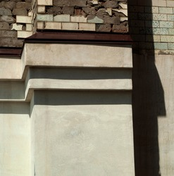 Part of the exterior wall of an old building with ledges like steps. Upper part is finished with tiles and concrete. Lower part is plastered. Different textures. Bright light. Neutral colors. Vertical