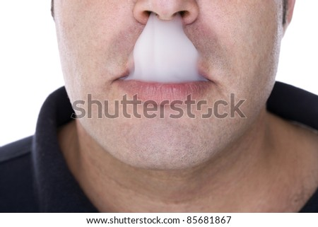 part of the face of a boy with a mouthful of smoke