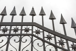 Part of the forged lattice of a black iron fence with arrows, stars and hearts