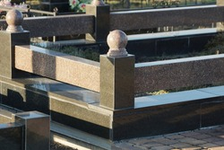 part of the gray marble fence stands on black slabs at the grave in the cemetery
