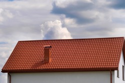 Part of the house with a brown tiled roof against the background of clouds.