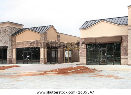 "Part of the ""instant village"" series.  A suburban strip center under construction in Atlanta.  Earth tone varied materials.  A shopping center made to appear like a small village street."