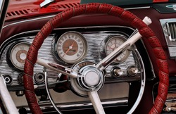 Part of the interior of an oldtimer sports luxury car with steering wheel, speedometer, fuel, clock dials, gear lever, front panel.