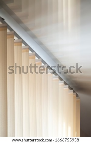 Part of the mechanism of beige vertical blinds on the background of a mirror stretch ceiling. Stock photo ©