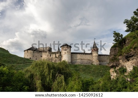 Part of the medieval Kamianets-Podilskyi fortress of the XVI century against the background of greenery and rocks in the foreground in the cloudy sky. Ukraine #1425092612