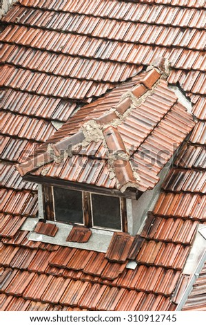 Part of the roof of old townhouse with wet from rain tiles