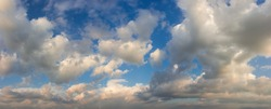 Part of the sky with cumulus clouds in summer evening time before sunset, panoramic view