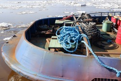 part of the stern of the tug with different ropes and a barrel against the background of the River, ice drift is known in the north. close-up.