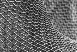 Part of the surface of metal sculpture. Beautiful abstract texture of the metal construction as background for design.  Filled full frame picture. Bent metal net with smooth convex curved shapes.