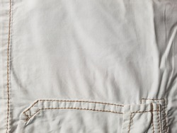 Part of the surface of white jeans with side pocket and seams as background.